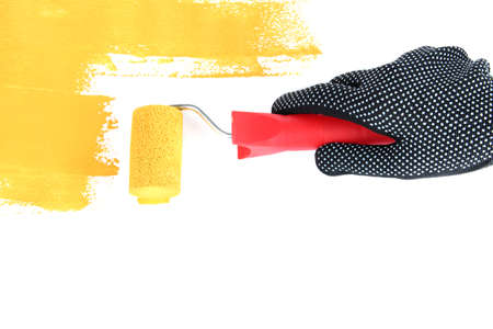 modernise: Roller brush with yellow paint in hand closeup Stock Photo