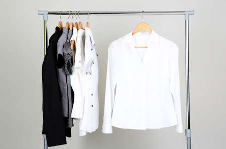 white shirt: Office clothes on hangers, on gray background Stock Photo