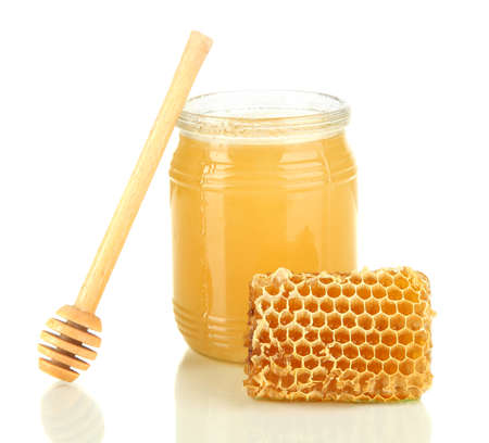 Sweet honeycomb and bank with honey isolated on white photo