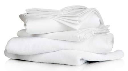 Stapel schone beddengoed lakens en handdoeken op wit wordt geïsoleerd