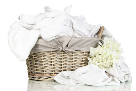 Rumpled bedding sheets in wicker basket isolated on white Stock Photo - 22341960