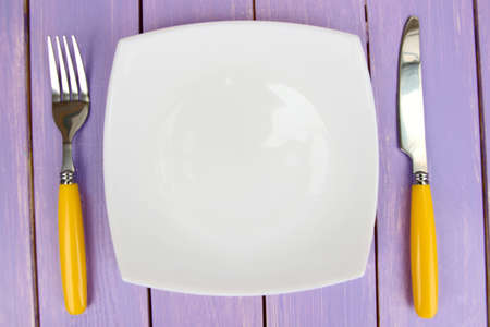 Plate and cutlery on wooden table close-up Stock Photo - 22342007