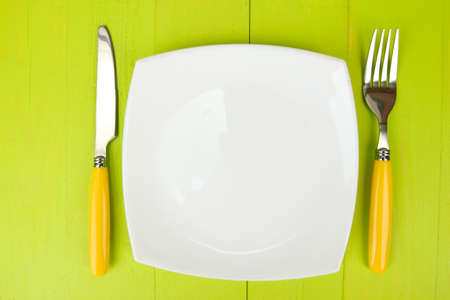 Plate and cutlery on wooden table close-up Stock Photo - 22342009