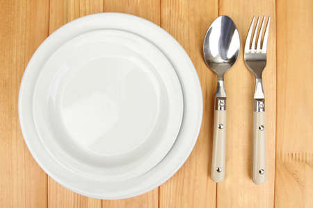 Plate and cutlery on wooden table close-up Stock Photo - 22342011