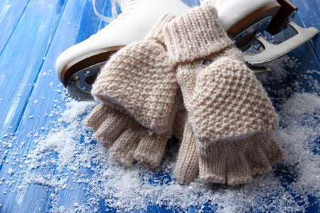 Wool fingerless gloves and skates for figure skating, on wooden background Stock Photo - 22364138