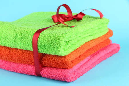 Towels tied with ribbon on light blue background