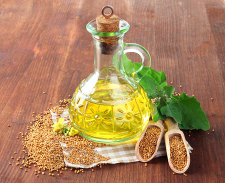 mustard leaf: Jar of mustard oil and seeds with mustard flower on wooden background Stock Photo