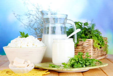 Fresh dairy products with greens on wooden table on natural background photo