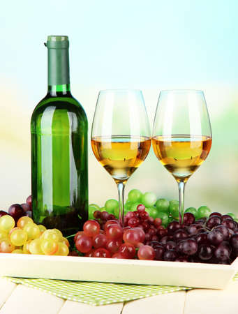 Ripe grapes, bottle and glasses of wine on tray, on bright background Stock Photo - 22462632