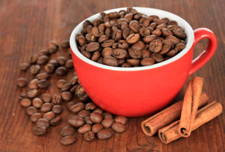 Coffee beans in cup on wooden background photo