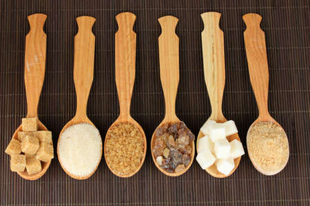 Different types of sugar in spoons on table close-up photo