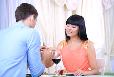 Man proposing engagement ring his woman over restaurant table photo