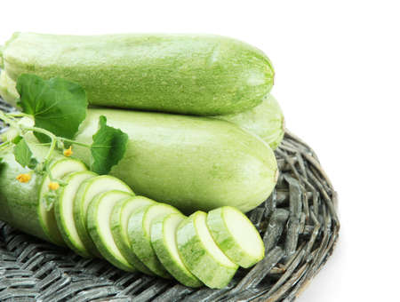 Sliced and whole raw zucchini, isolated on white Фото со стока