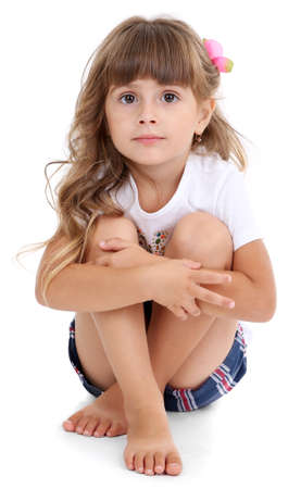 Little girl sitting on floor isolated on white photo