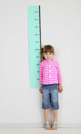 Little girl measuring height against wall in room photo