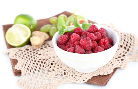 Raspberries in small bowl on napkin isolated on white photo