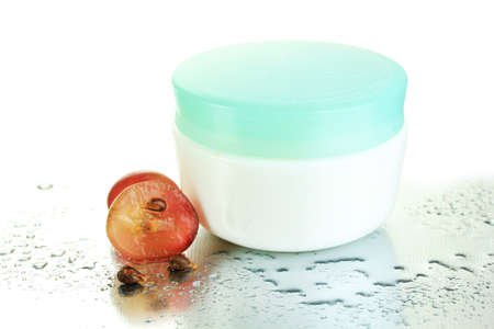 Cosmetic cream and sliced grape, close up photo