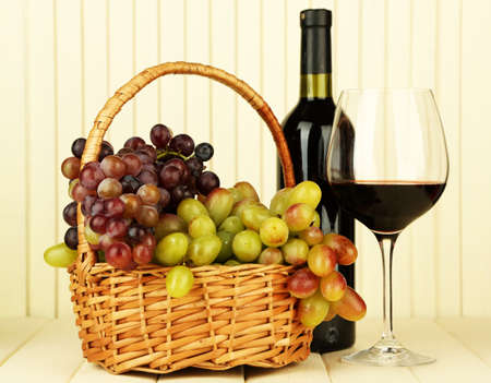 Ripe grapes in wicker basket, bottle and glass of wine photo