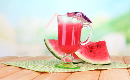Glass of fresh watermelon juice, on wooden table photo