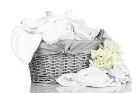 Rumpled bedding sheets in wicker basket isolated on white photo