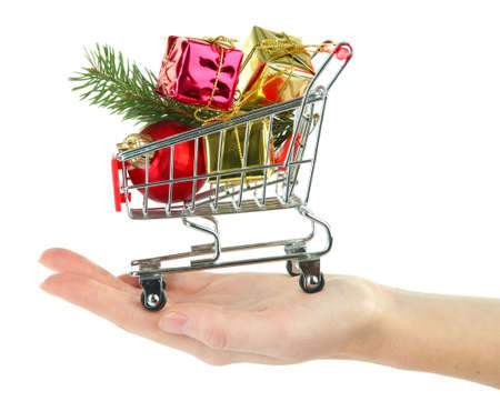 Hand holding Christmas gifts in shopping trolley, isolated on white photo