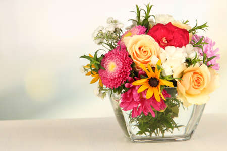 mixed flower bouquet: Beautiful bouquet of bright flowers in glass vase, on wooden table, on bright background
