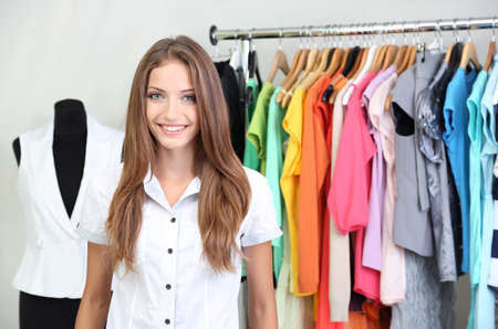Beautiful young stylist near rack with hangers Stock Photo - 23303473