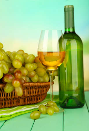 Ripe grapes in wicker basket, bottle and glass of wine, on bright background photo