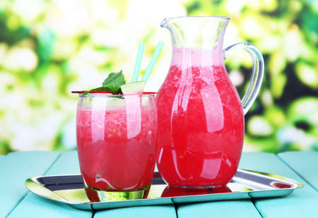 Glass of fresh watermelon juice, on wooden table, on bright background photo
