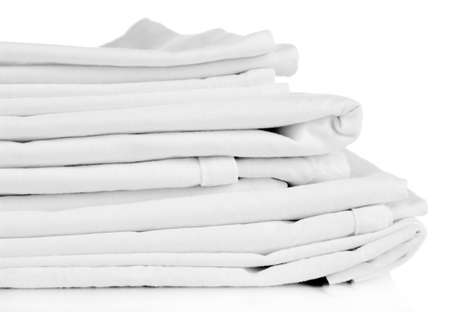 Stack of clean bedding sheets isolated on white photo