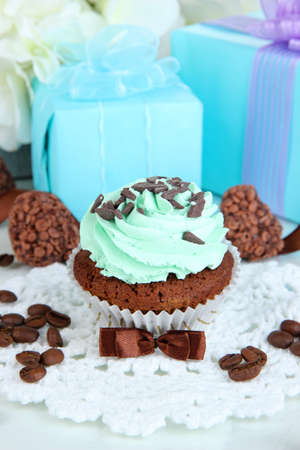 Tasty cupcake with gifts close up photo