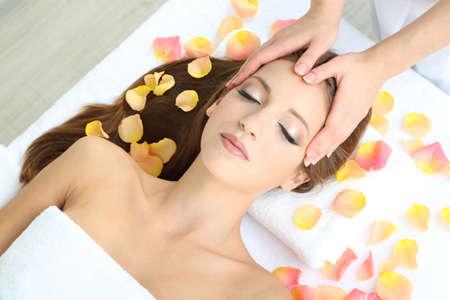 pulizia viso: Giovane e bella donna durante il massaggio del viso nel salone cosmetico da vicino