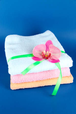 orange washcloth: Towels tied with ribbon on blue background