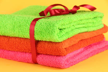 orange washcloth: Towels tied with ribbon close-up