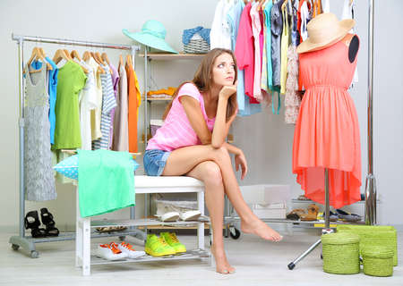 clothes store: Beautiful girl thinking what to dress in walk-in closet