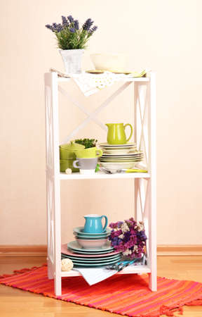 Beautiful white shelves with tableware and decor, on color wall background photo