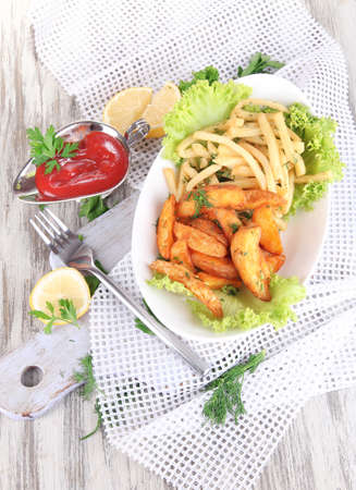 French fries and home potatoes on plate on board on napkin on wooden table photo