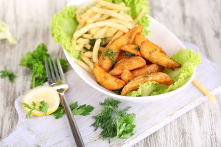 French fries and home potatoes on plate on board on wooden table photo