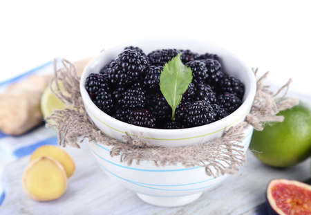 Blackberry in small bowl on board on napkin isolated on white photo