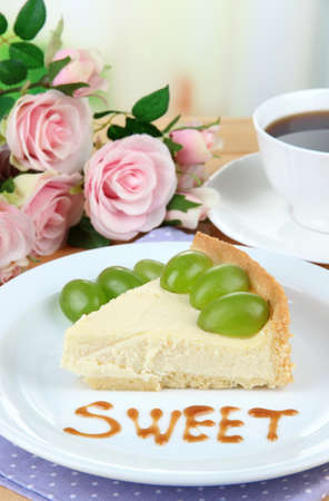 cheese cake: Slice of cheesecake with grape berries on plate, on wooden table, on bright background Stock Photo