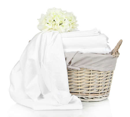 Bedding sheets in wicker basket isolated on white photo