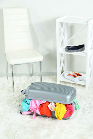 Suitcase with clothes on carpet on room background Stock Photo - 22620292