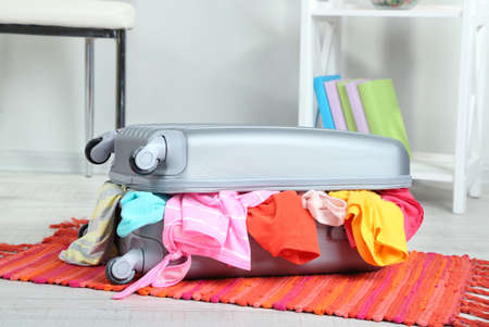 Suitcase with clothes on mat on room background Stock Photo - 22620294