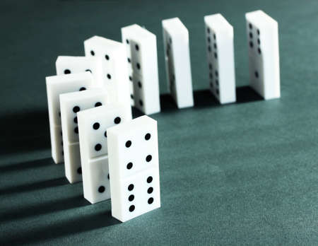 cause and effect: Dominoes on grey background