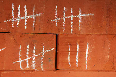 unfreedom: Counting days by drawing sticks on bricks close up