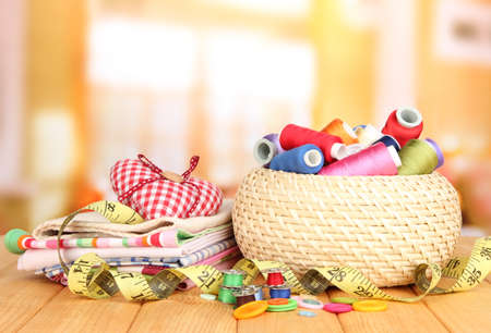 Wicker basket with accessories for needlework on wooden table photo
