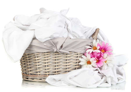 laundry concept: Rumpled bedding sheets in wicker basket isolated on white