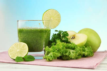 Glass of green vegetable juice on wooden table  photo