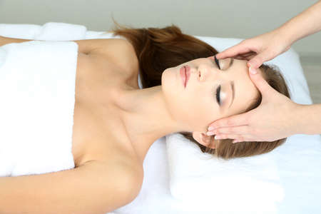 Beautiful young woman during facial massage in cosmetic salon close up photo