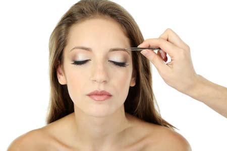 tweezing eyebrow: Young woman having eye-brows plucked isolated on white
